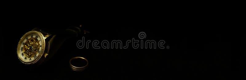 Os rel?gios de pulso e um anel dos homens em um veludo preto imagem de stock royalty free