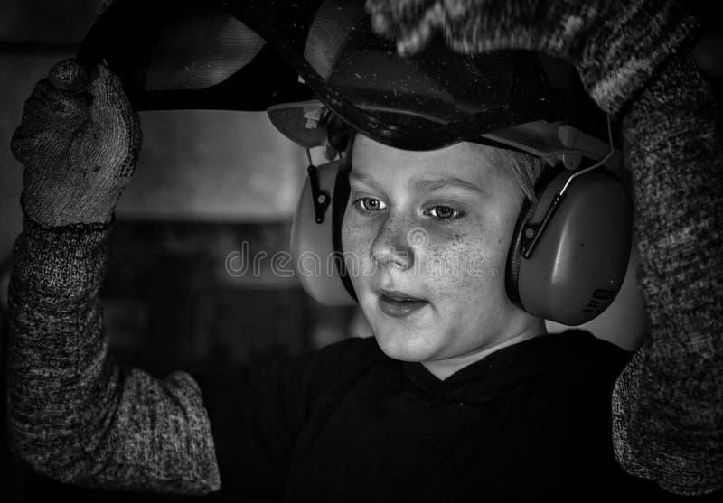 Os reparos do rapaz pequeno molham caldeiras no porão fotografia de stock royalty free