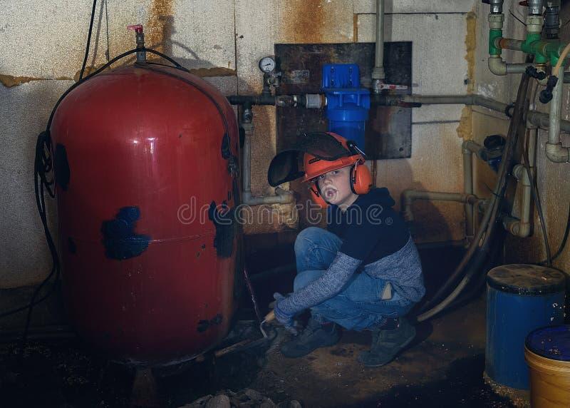 Os reparos do rapaz pequeno molham caldeiras no porão foto de stock royalty free