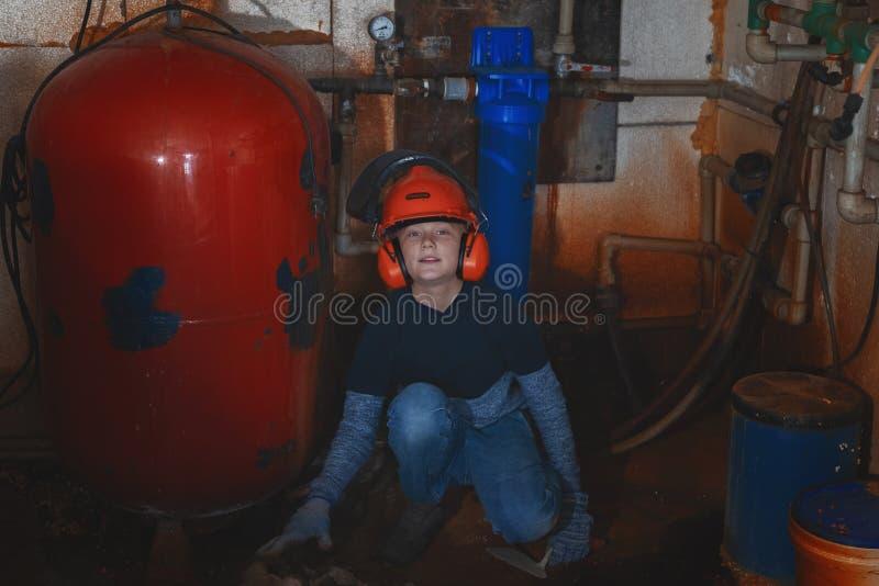 Os reparos do rapaz pequeno molham caldeiras no porão imagem de stock royalty free