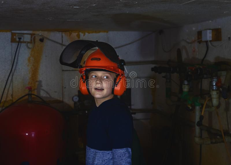 Os reparos do rapaz pequeno molham caldeiras no porão fotografia de stock