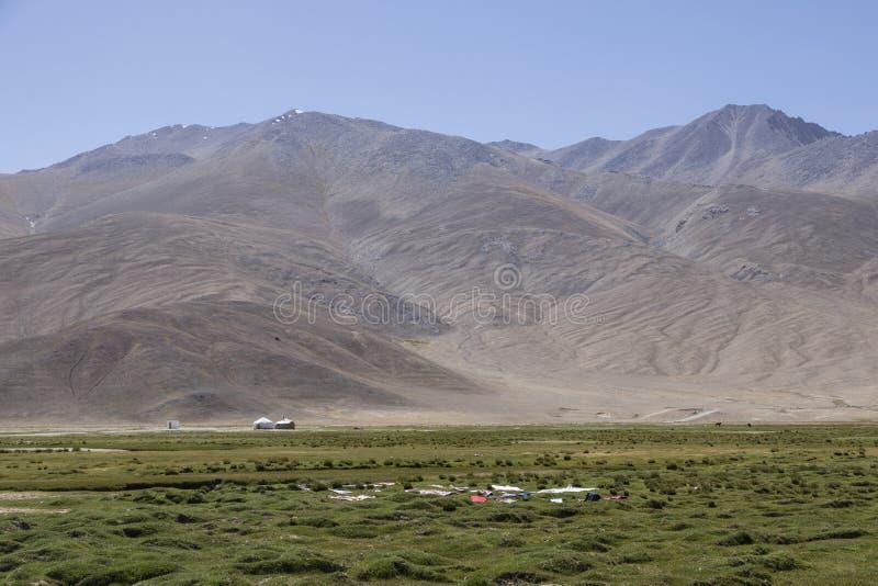 Os residentes de Bulunkul em Tajiquistão projetaram as lavagens secar na grama fotos de stock