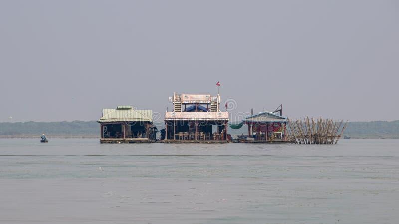 Os restaurantes e as lojas de flutuação estão em pernas de pau na vila do rio imagens de stock