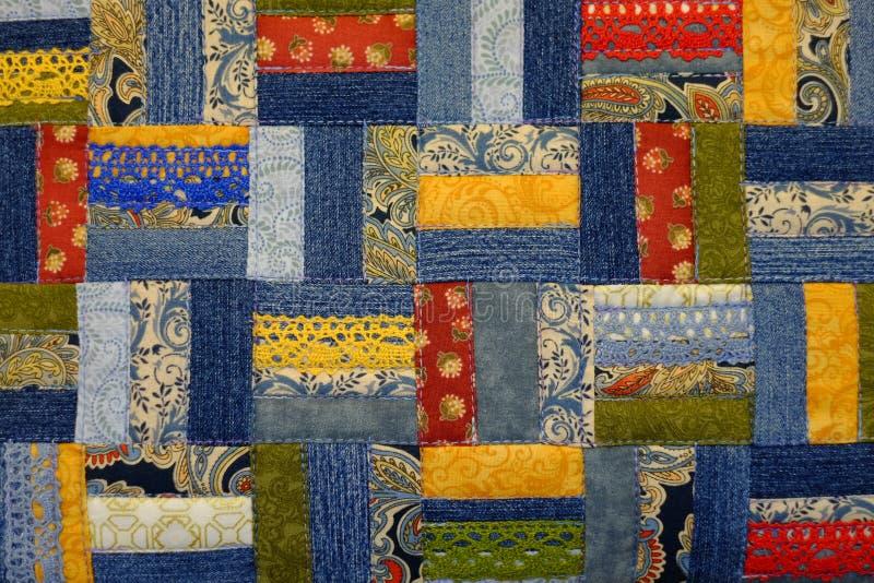 Os retalhos feitos a mão feitos do teste padrão da sarja de Nimes azul, retalhos coloridos e fitas do laço fotos de stock royalty free
