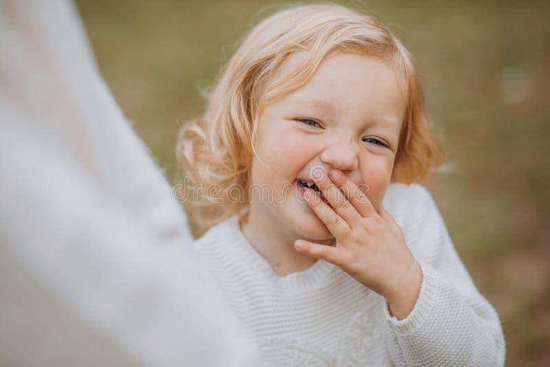 Os risos da menina cobrem o parque da mamã da caminhada da mão da cara fotos de stock