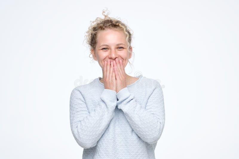 Os risos encaracolados caucasianos novos alegremente, cobrem a boca enquanto as tentativas param de rir imagem de stock royalty free
