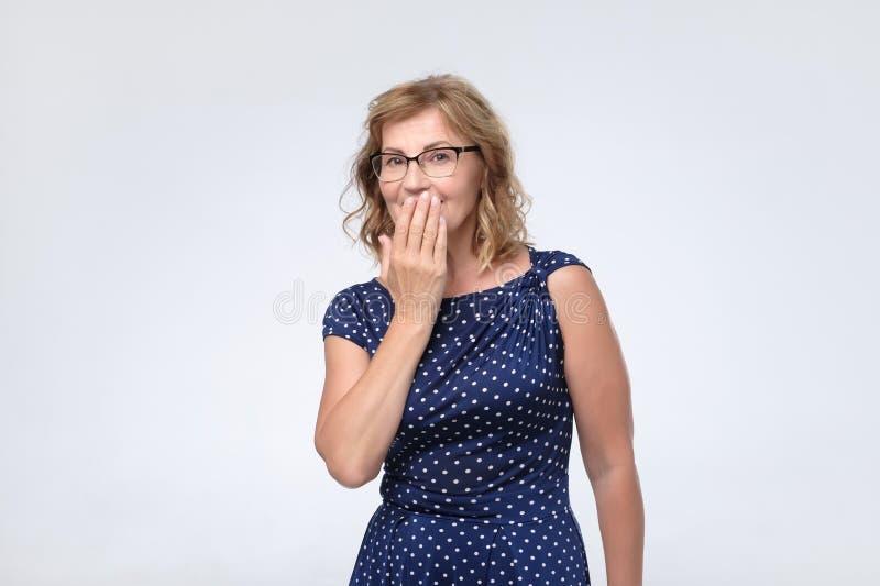 Os risos maduros bonitos da mãe da mulher alegremente, cobrem a boca enquanto as tentativas param de rir fotografia de stock