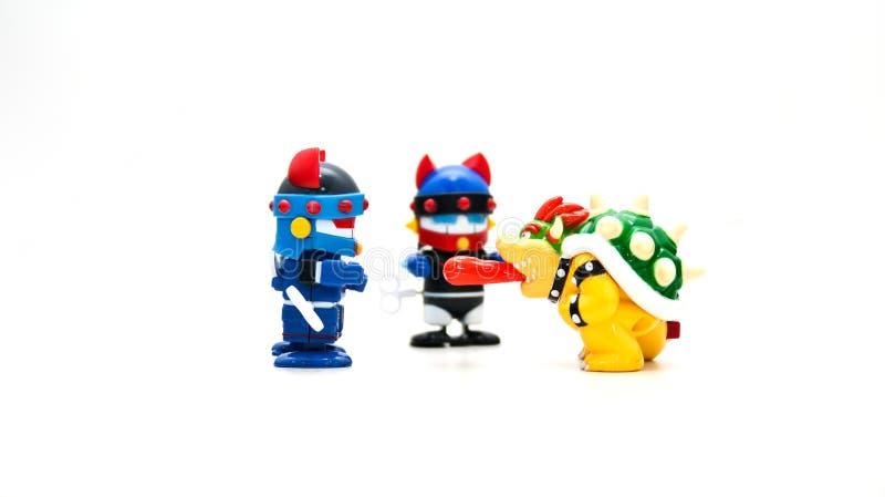 Os robôs que vestem dois capacetes azuis em um fundo branco estão pagando a atenção aos monstro que têm sua língua vermelha para  fotografia de stock royalty free
