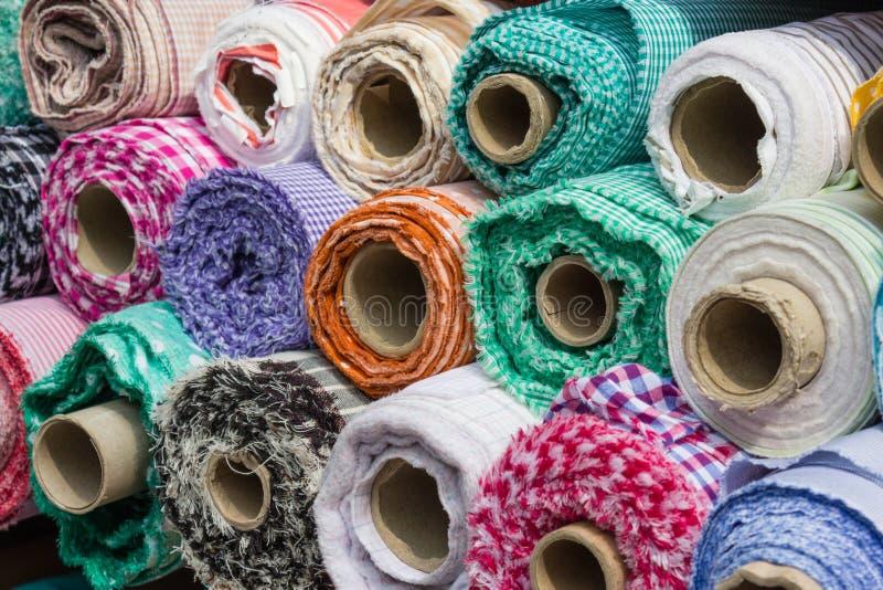 Os rolos da tela no mercado param, fundo da indústria têxtil imagem de stock