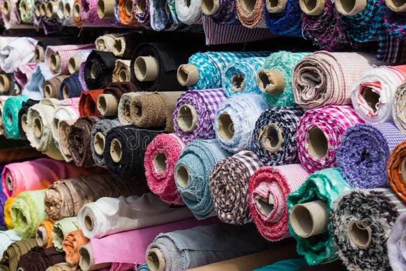 Os rolos da tela no mercado param, fundo da indústria têxtil foto de stock