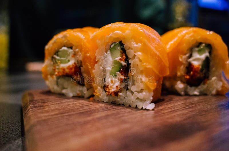 Os rolos de sushi cortaram em uma bandeja de madeira estão na tabela pronto para comer fotos de stock