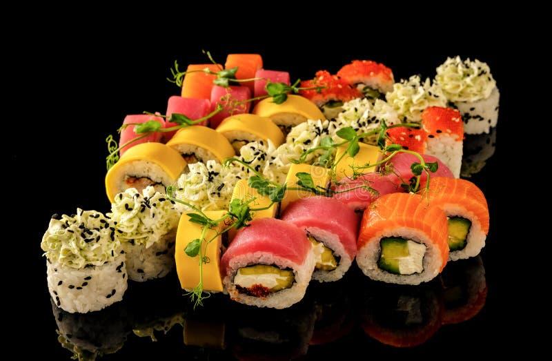 Os rolos de sushi frescos ajustados serviram no fundo preto Seafo japonês imagem de stock royalty free