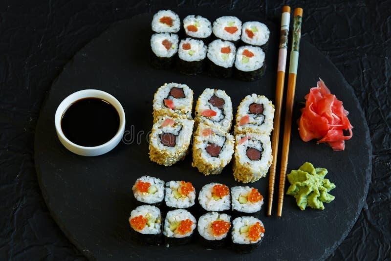 Os rolos de sushi serviram no caviar de pedra do vermelho da ardósia imagem de stock