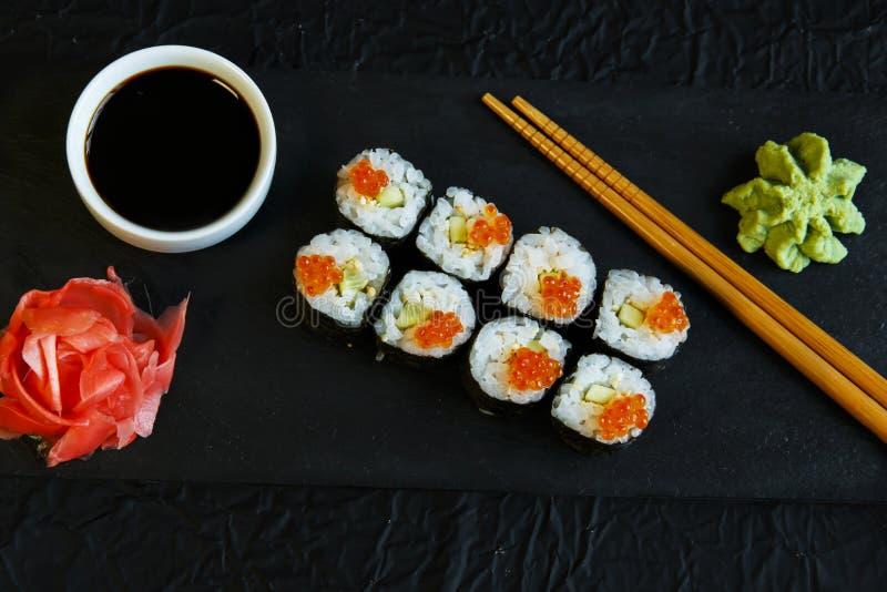 Os rolos de sushi serviram no caviar de pedra do vermelho da ardósia fotografia de stock royalty free