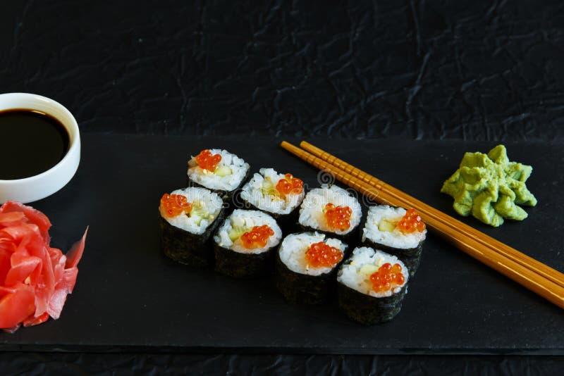 Os rolos de sushi serviram no caviar de pedra do vermelho da ardósia imagem de stock royalty free