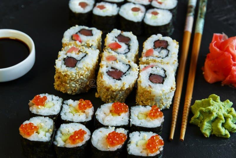 Os rolos de sushi serviram no caviar de pedra do vermelho da ardósia foto de stock royalty free