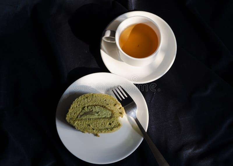 Os rolos deliciosos do bolo do matcha e um copo do chá verde imagens de stock