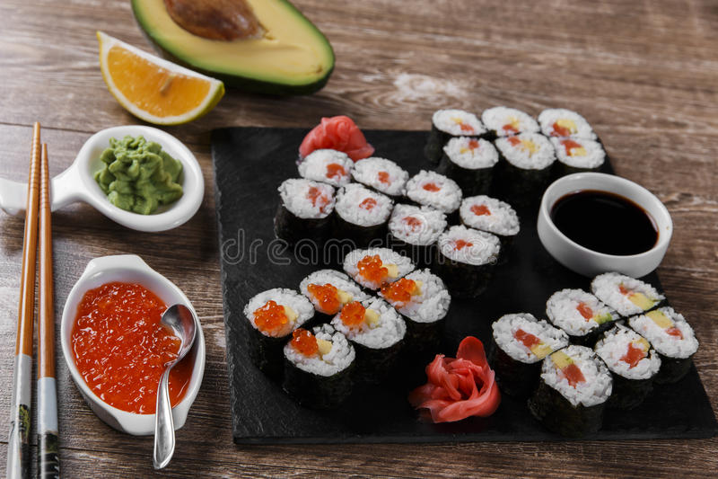 Os rolos e os ingredientes de sushi serviram em uma superfície de madeira imagens de stock royalty free