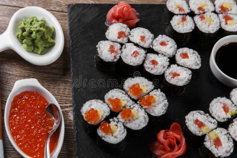 Os rolos e os ingredientes de sushi serviram em uma superfície de madeira fotos de stock