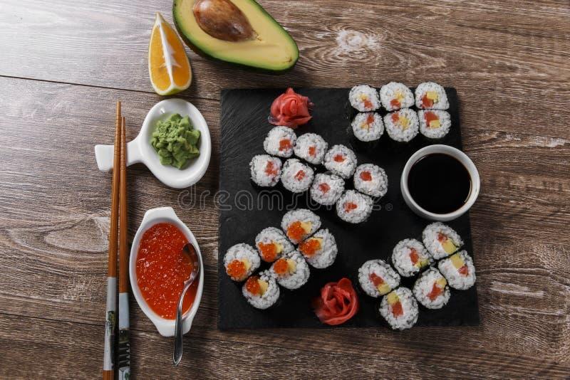 Os rolos e os ingredientes de sushi serviram em uma superfície de madeira fotografia de stock royalty free