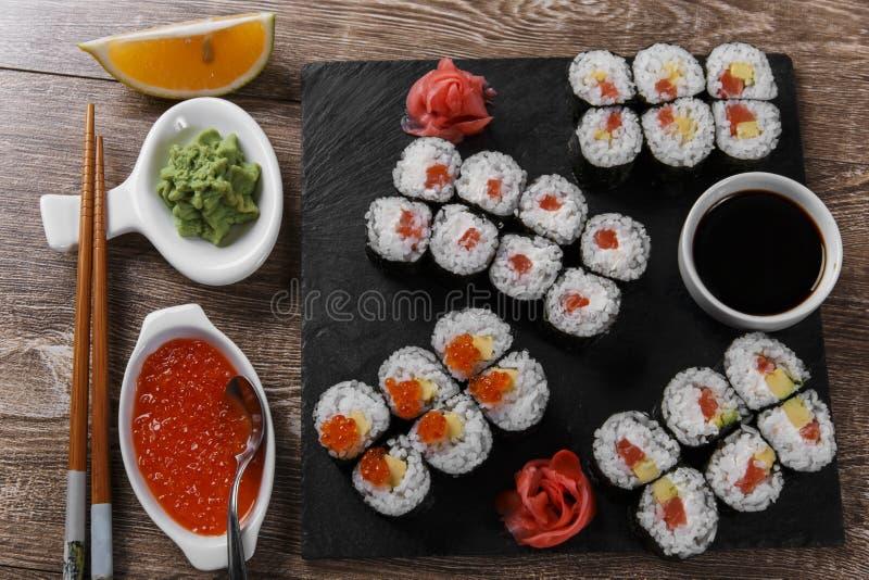 Os rolos e os ingredientes de sushi serviram em uma superfície de madeira fotografia de stock