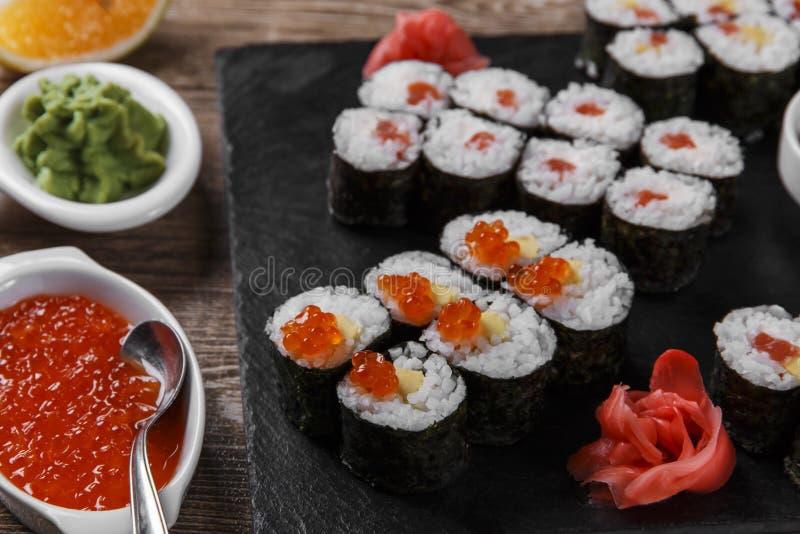 Os rolos e os ingredientes de sushi serviram em uma superfície de madeira imagens de stock
