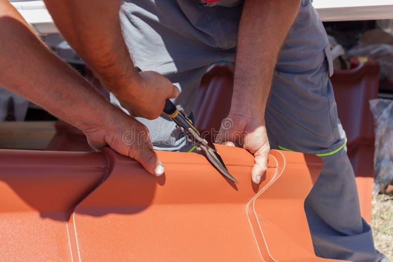 Os Roofers cortaram uma telha do metal usando alicates do corte fotos de stock royalty free