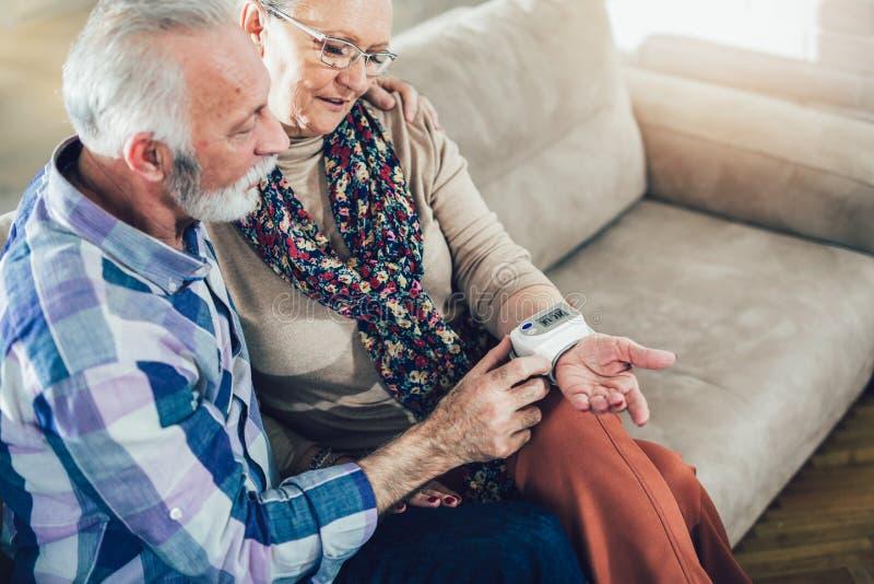Os séniores acoplam em casa a pressão sanguínea de medição imagens de stock