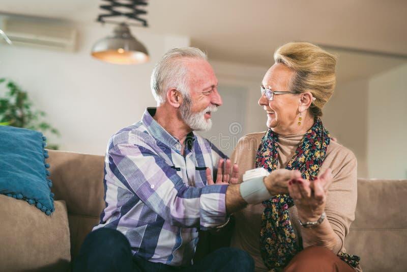 Os séniores acoplam em casa a pressão sanguínea de medição fotos de stock royalty free