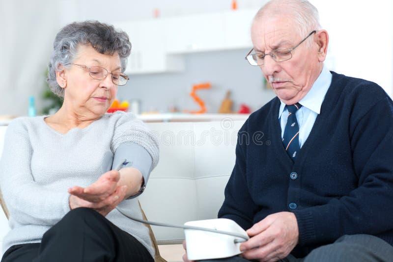 Os séniores acoplam em casa a pressão sanguínea de medição imagens de stock royalty free