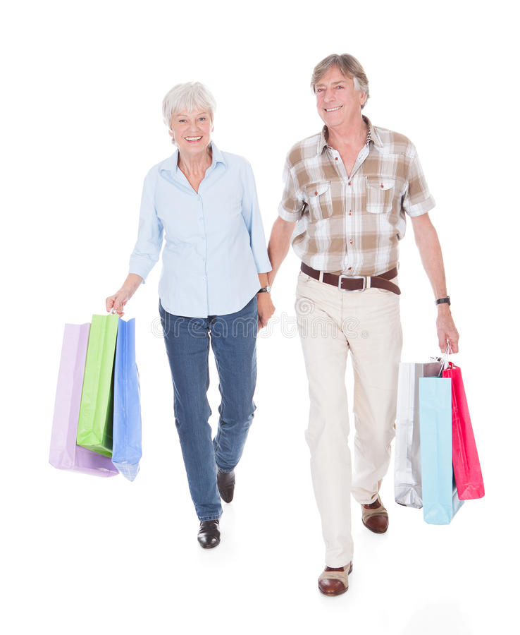 Os sêniores acoplam o passeio com saco de compras fotos de stock