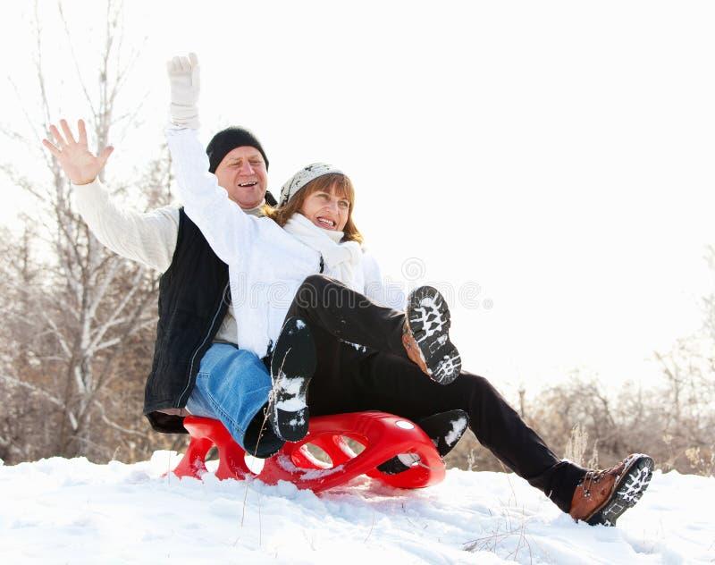 Os sêniores acoplam-se no trenó no parque do inverno foto de stock