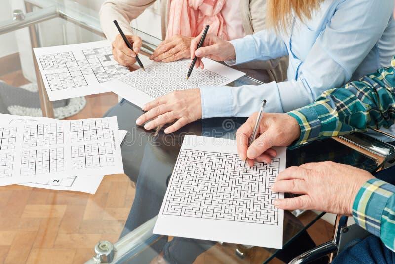 Os sêniores estão fazendo o treinamento da memória com labirinto imagens de stock