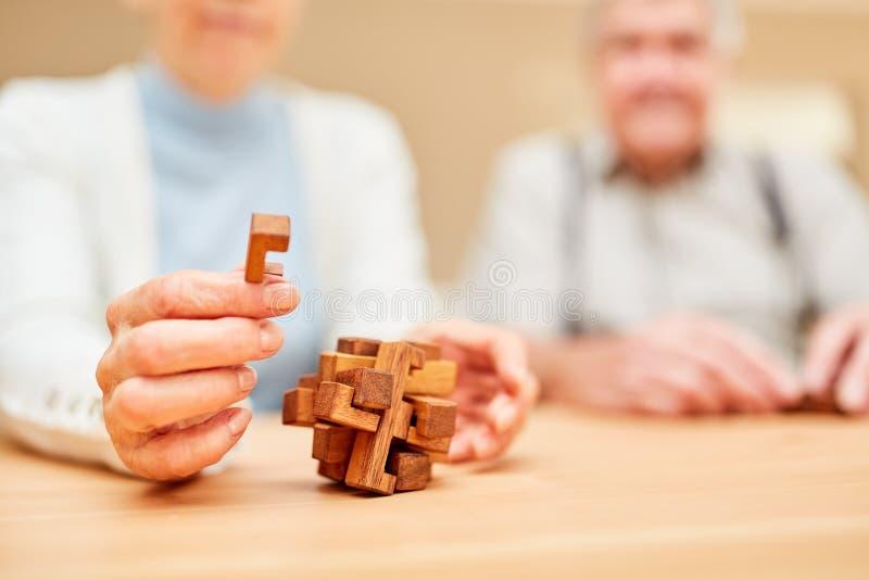 Os sêniores estão fazendo um jogo do enigma com enigma de madeira imagem de stock