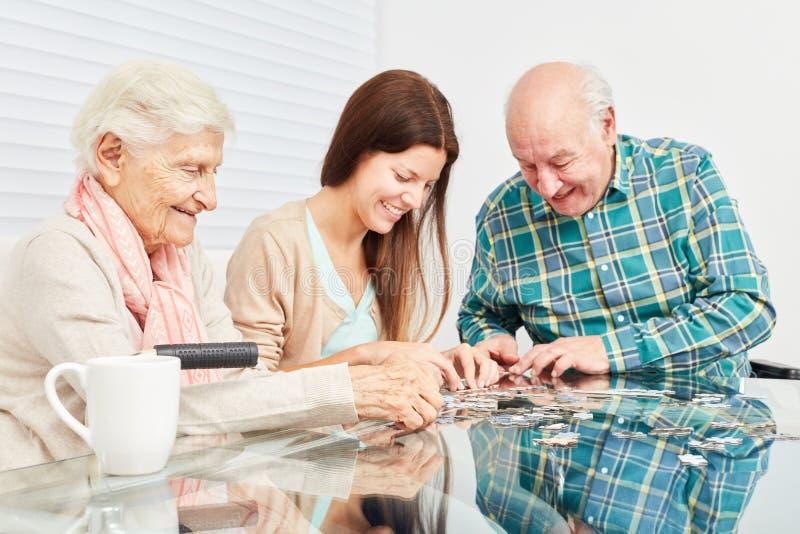 Os sêniores jogam o enigma como um treinamento da memória fotos de stock royalty free