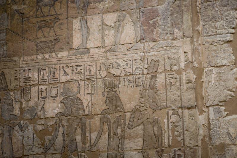 Os símbolos assinam figuras dos Pharaohs em Egito, a parede em Luxo foto de stock royalty free