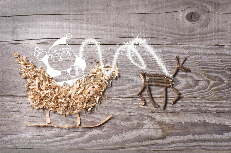 Os símbolos simples do trenó de Christmas do pai arranjaram da serragem e da rena feitas das varas de madeira secas no fundo cinz foto de stock royalty free