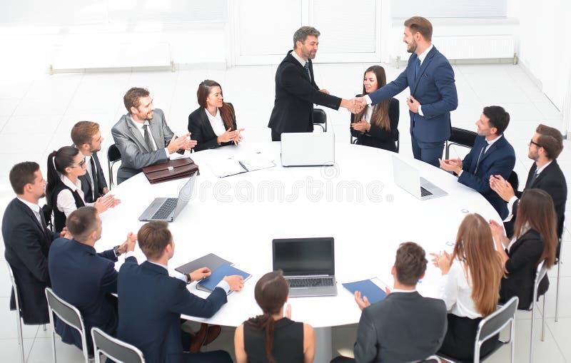 Os sócios comerciais agitam as mãos nas negociações perto da mesa redonda fotos de stock