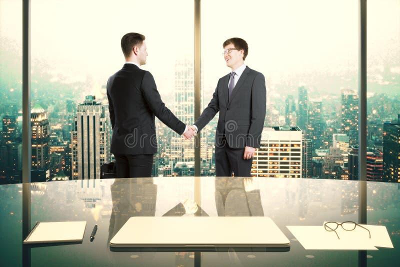 Os sócios comerciais agitam as mãos no escritório moderno com megapo da noite foto de stock royalty free