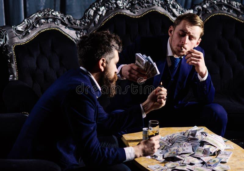 Os sócios comerciais com caras seguras guardam dólares e vidro do champanhe Mobília do vintage, caro, superior, dinheiro foto de stock royalty free