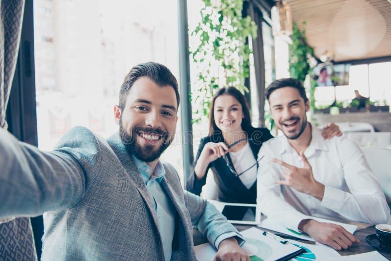 Os sócios comerciais felizes dos amigos estão fazendo a foto do selfie, sentando-se fotos de stock royalty free