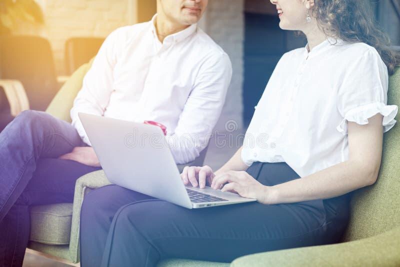 Os sócios comerciais novos estão trabalhando junto, usando o portátil no escritório, discutindo a partida criativa da ideia foto de stock royalty free
