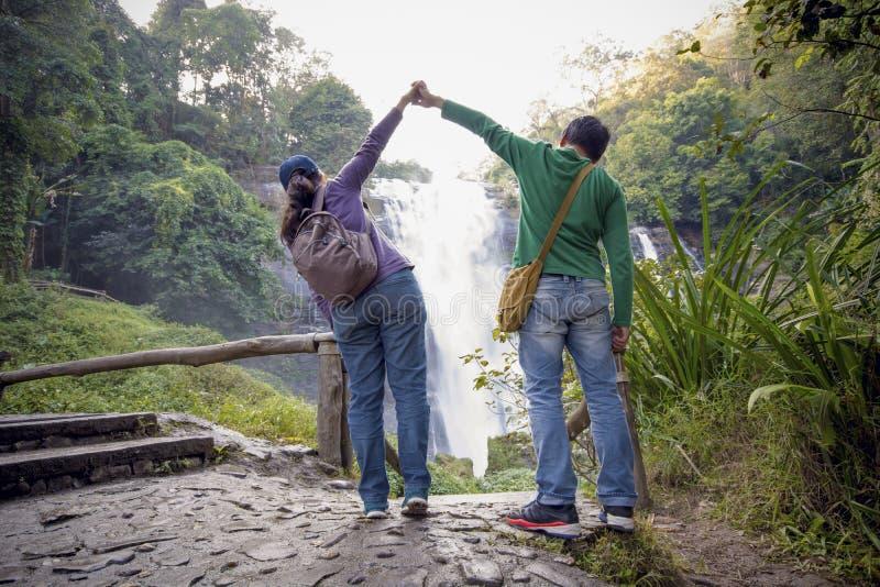 Os sócios masculinos e fêmeas guardam as mãos e levantam suas mãos imagem de stock royalty free