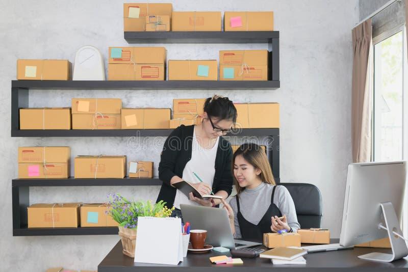 Os sócios ou os proprietários empresariais asiáticos novos do empresário trabalham em casa o escritório que verificam a ordem do  fotos de stock