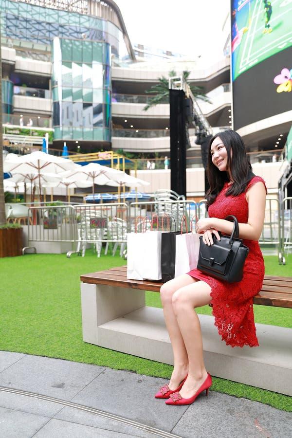 Os sacos de compra do cartão dos pés modernos chineses asiáticos bonitos da menina da mulher elegante em um close up ocasional do fotografia de stock