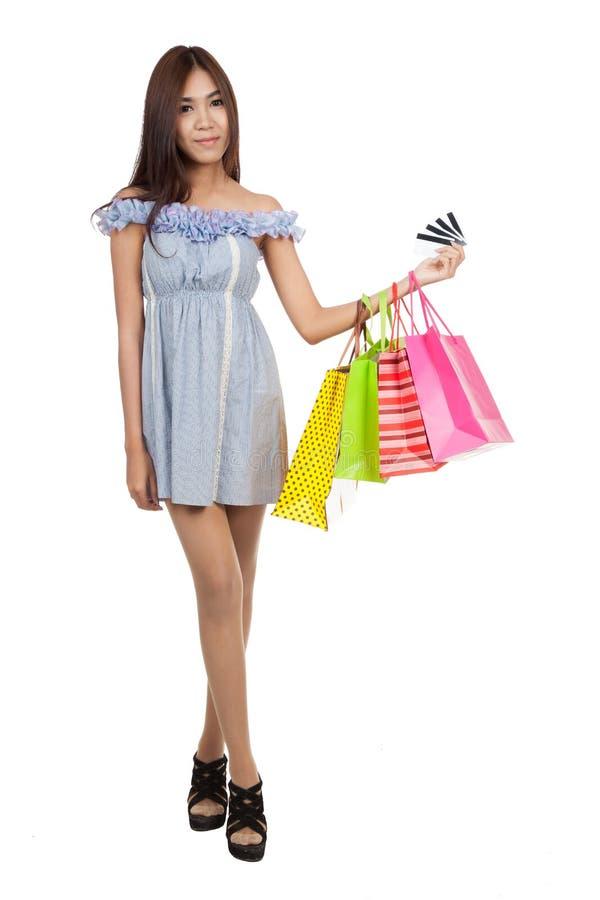 Os sacos de compras asiáticos bonitos da posse da mulher mostram muitos cartões de crédito foto de stock royalty free