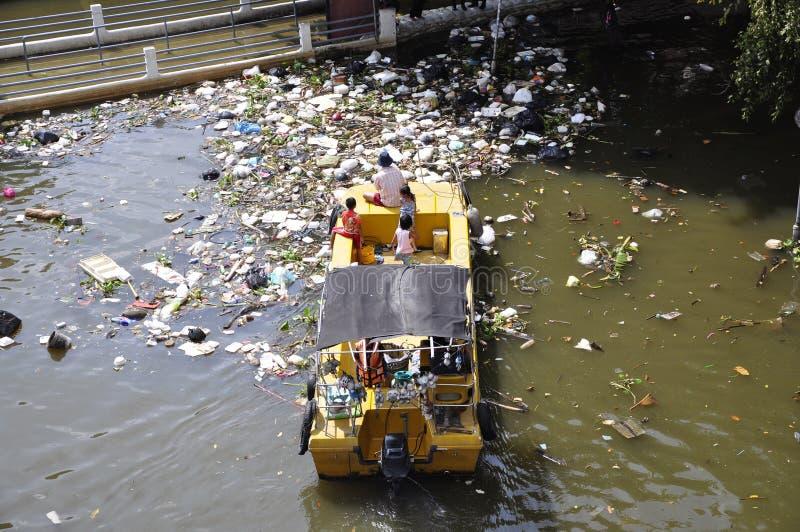 Os sacos de plástico e o outro lixo flutuam no rio Chao Phraya