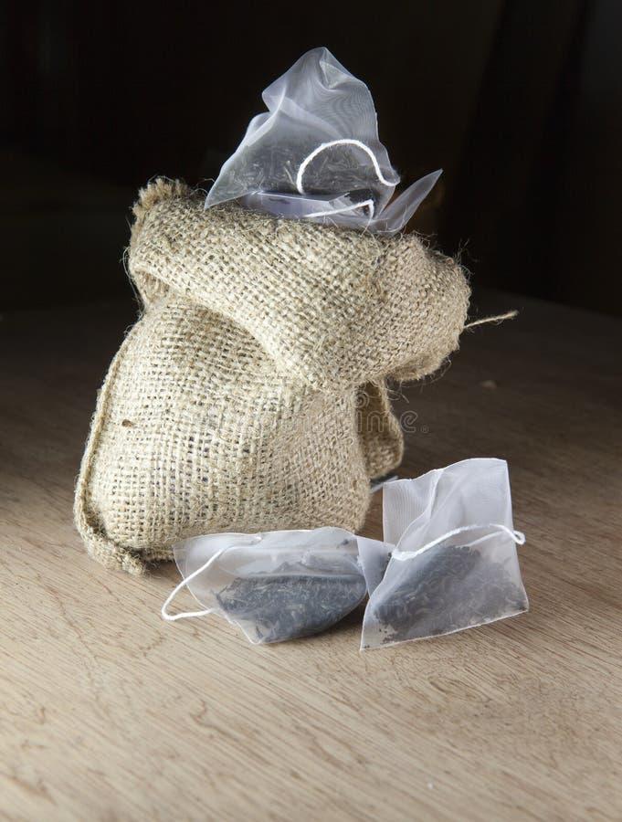 Os sacos do chá da elite na embalagem da tela de seda em uma lona ensacam em um fundo de madeira imagem de stock royalty free