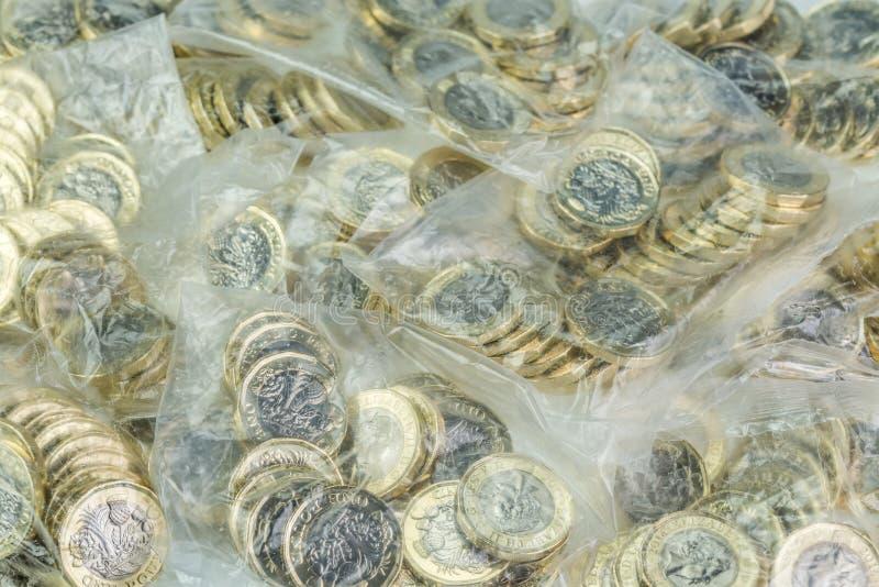 Os sacos do dinheiro encheram com os Ingleses moedas de uma libra fotos de stock