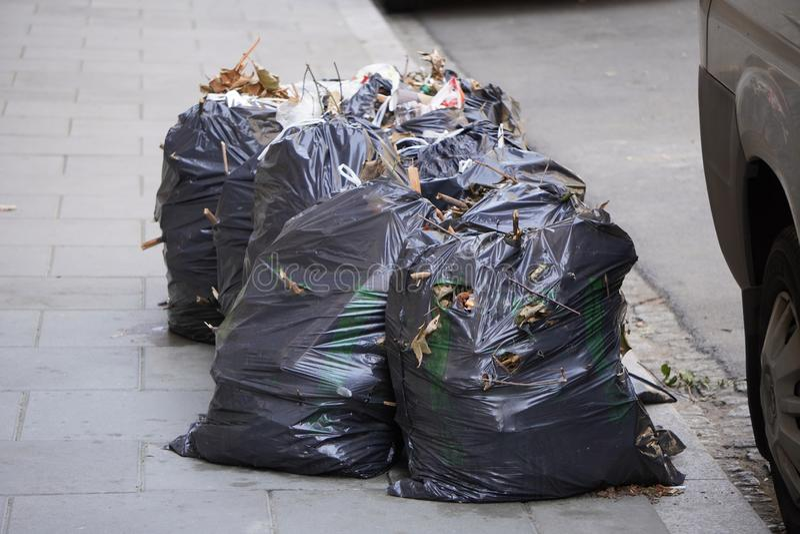 Os sacos pretos, atados do lixo do agregado familiar estão na estrada para carregar no caminhão de lixo desperdice classificando, foto de stock royalty free